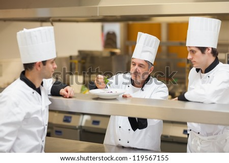 Head chef showing others how to garnish plate at order line - stock photo