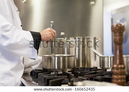 Head chef stirring in pot in professional kitchen - stock photo