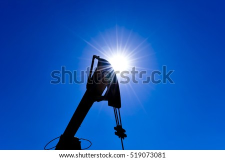 Head counterweight oil pump jack backlit. Oil equipment against the sky and sun.
