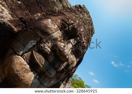 Head encarved in stone Bayon temple Angkor Wat Cambodia - stock photo