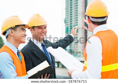 Head engineer telling customers about the project of the building - stock photo