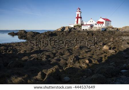 Head Harbor lighthouse in Canada with its distinctive red cross at low tide.