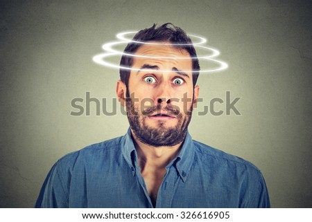 Head is spinning. Surprise astonished man. Closeup portrait man looking surprised in full disbelief wide open mouth isolated grey wall background. Human emotion face expression body language. - stock photo