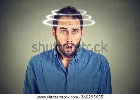 Head is spinning. Surprise astonished man. Closeup portrait man looking surprised in full disbelief wide open mouth isolated grey wall background. Human emotion face expression body language reaction  - stock photo
