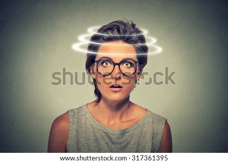 Head is spinning. Surprise astonished woman. Closeup portrait woman looking surprised in full disbelief open mouth isolated on grey wall background. Human emotion face expression body language. - stock photo
