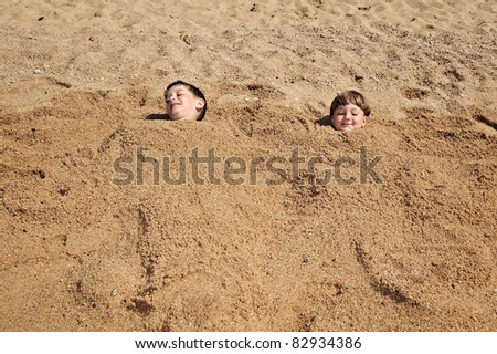 head of a boys buried in the sand - stock photo