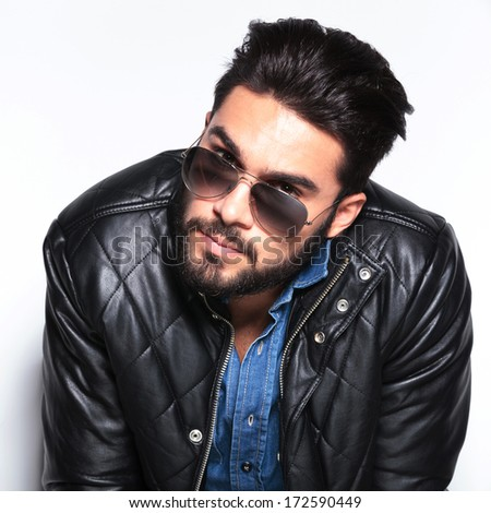 head of a young man with sunglasses looking to the camera in studio - stock photo