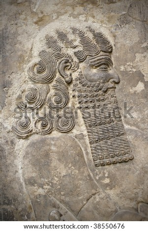 Head of an ancient assyrian warrior carved in stone - stock photo