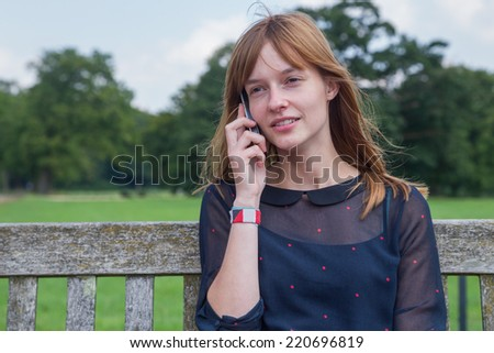 Head of blond girl with water and green trees - stock photo
