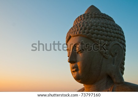 head of buddha statue isolated against dawn or dusk sky - stock photo