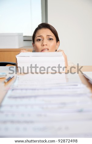 Head of businesswoman behind large pile of papers - stock photo