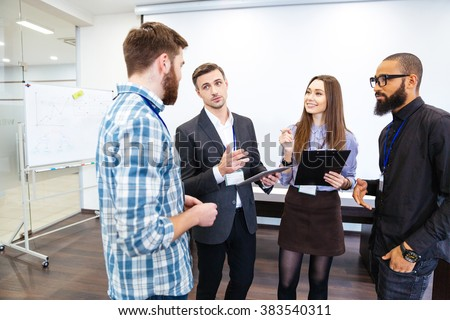Head of department standing and talking to smiling young employees in office - stock photo