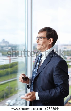 Head of drinking coffee by the window in the office - stock photo