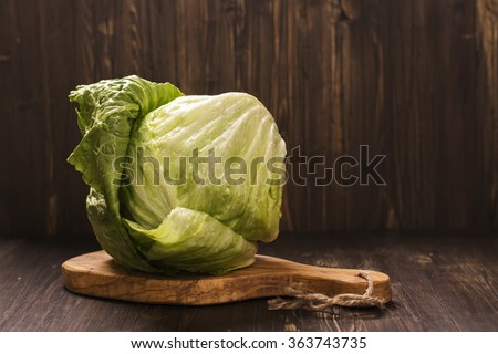 Head of fresh organic iceberg lettuce over vintage wooden background. Selective focus - stock photo