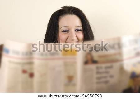 Head of laughing woman reading the news - stock photo