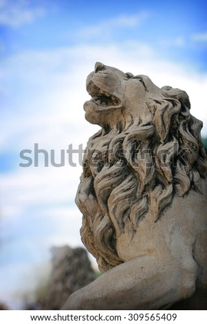 Head of stone lion statue on background blue sky - stock photo