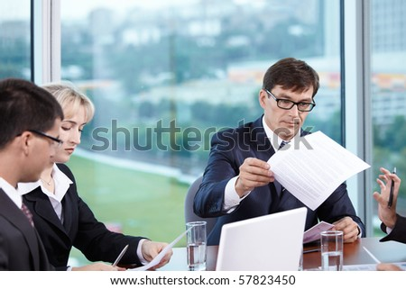 Head of the meeting distributes copies of his subordinates - stock photo