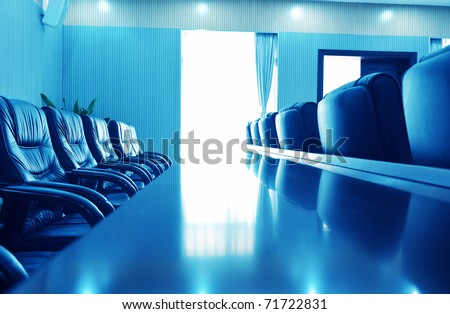 Head office boardroom with leather chairs, blue tone. - stock photo