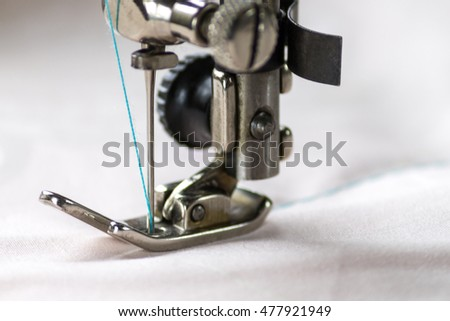 head old vintage sewing machine in working stitches through the stitch on the fabric closeup