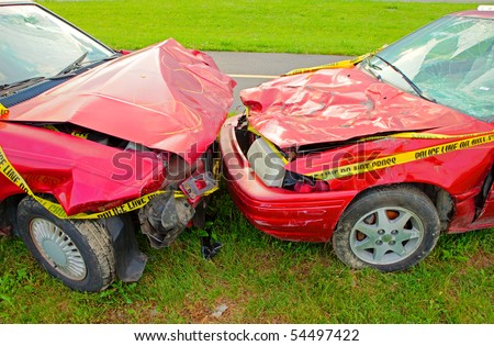 Head On Collision of Two Red Cars both with cracked windshields and smashed hoods. - stock photo