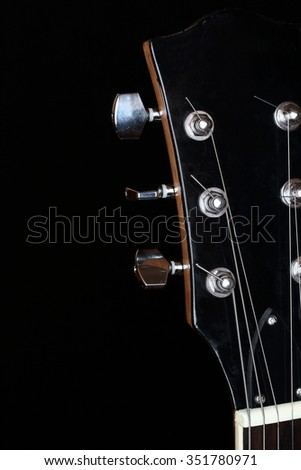 head plate of an electric guitar on black background - stock photo