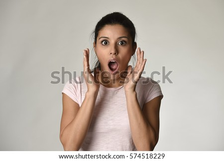 head portrait of young beautiful hispanic surprised woman amazed in shock and surprise with mouth big opened isolated grey background in astonished face expression