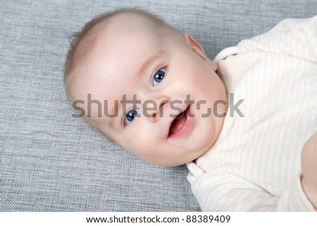 head shoot of cute baby with blue eyes and nice smile - stock photo