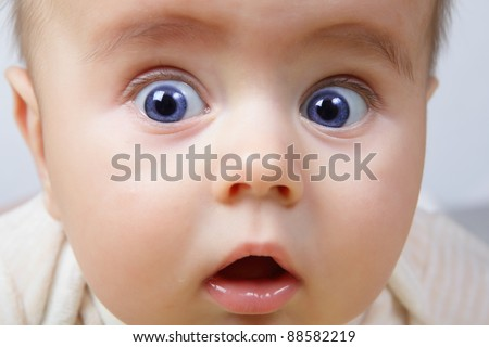 head shoot of cute baby with blue eyes and surprise look - stock photo