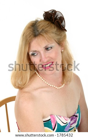 Head Shot of a Beautiful adorned middle aged woman sits back ready to go with Flower in Her Hair. - stock photo