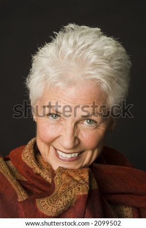 Head shot of a beautiful 55 to 60 year old woman against a black background. - stock photo