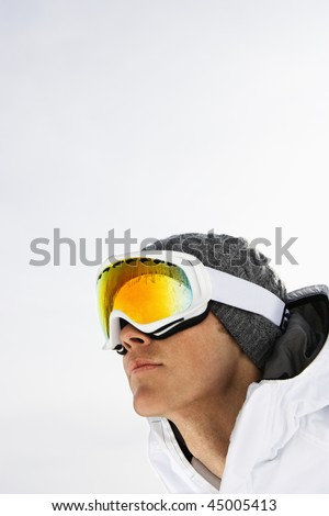 Head shot of a male skier wearing ski goggles against a snowy white background. Vertical shot.
