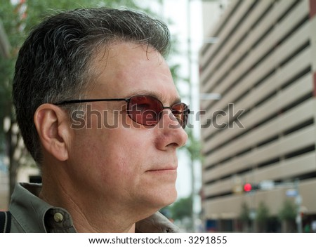 Head shot of a man in an urban setting with an expressionless face as if his thoughts are elsewhere. - stock photo