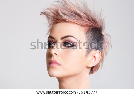 Head shot of a serious looking young woman sporting a pink punk haircut. Horizontal shot. - stock photo