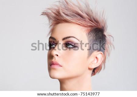Head shot of a serious looking young woman sporting a pink punk haircut. Horizontal shot. - stock photo