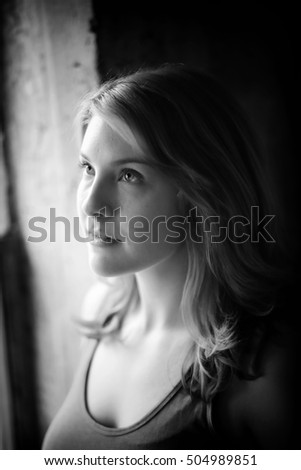 Head shot of a very attractive young woman shot in black in white window light.