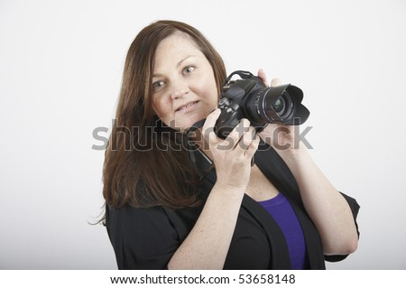 Head shot of a woman holding up a SLR camera