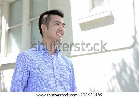 Head shot of a young Asian man smiling taken from a low angle