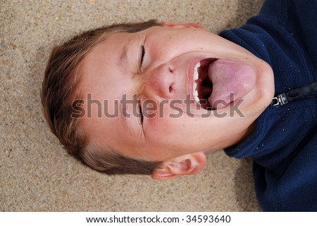 Head shot of a young boy with a silly face. - stock photo