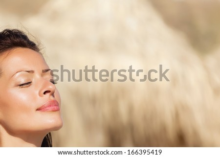 Head shot of beautiful woman enjoying the sunshine at a coast.Copy space - stock photo