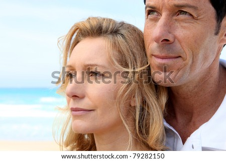 Head shot of couple by sea - stock photo