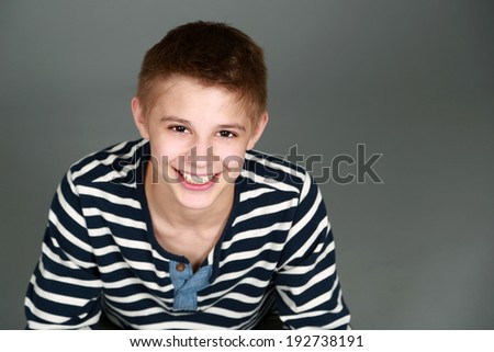 head shot of handsome preteen boy looking at camera smiling