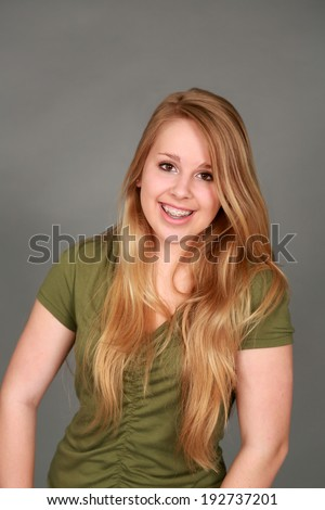 head shot of happy teen girl with blonde hair looking at camera - stock photo