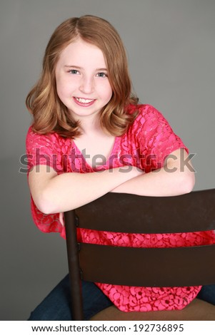 head shot of preteen girl smiling and looking at camera - stock photo