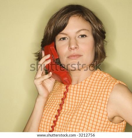 Head shot of pretty Caucasian mid-adult woman wearing orange dress listening to red telephone receiver. - stock photo