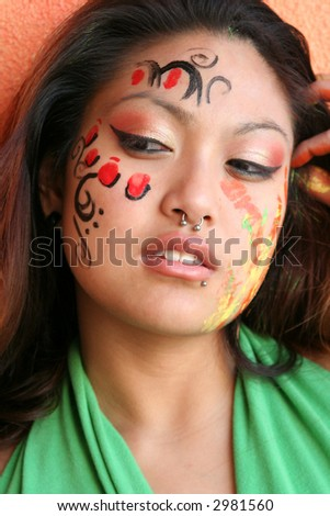 Head shot of young asian woman with piercing in nose and lip putting paint on her face