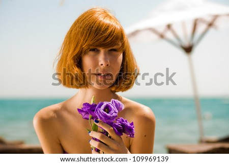 head shot portrait of a beautiful red haired sexy young woman holding purple rose & sitting outdoors on bright summer day on beach lounge on the blue sea & sky background - stock photo