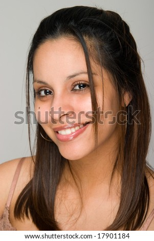 Head shot portrait of a young beautiful Hispanic woman. Limited depth-of-field with focus on model eye nearest the camera. - stock photo