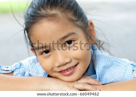 Head shot portrait of beautiful little asian girl in the park, Thailand. - stock photo