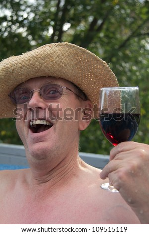 Head & shoulders of middle aged man in cowboy hat with one tooth missing and needing a shave, sitting in hot tub holding a glass of wine with green trees in the background.