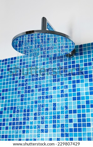 Head shower while running water against blue mosaic tiles - stock photo
